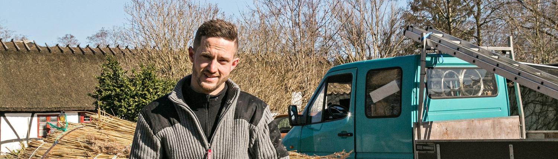 Tækkemand portræt med strå i baggrunden og turkis arbejdsbil