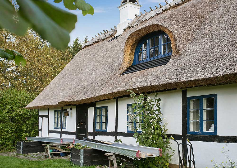 Nytækket stråtag på hvidt hus med kvist