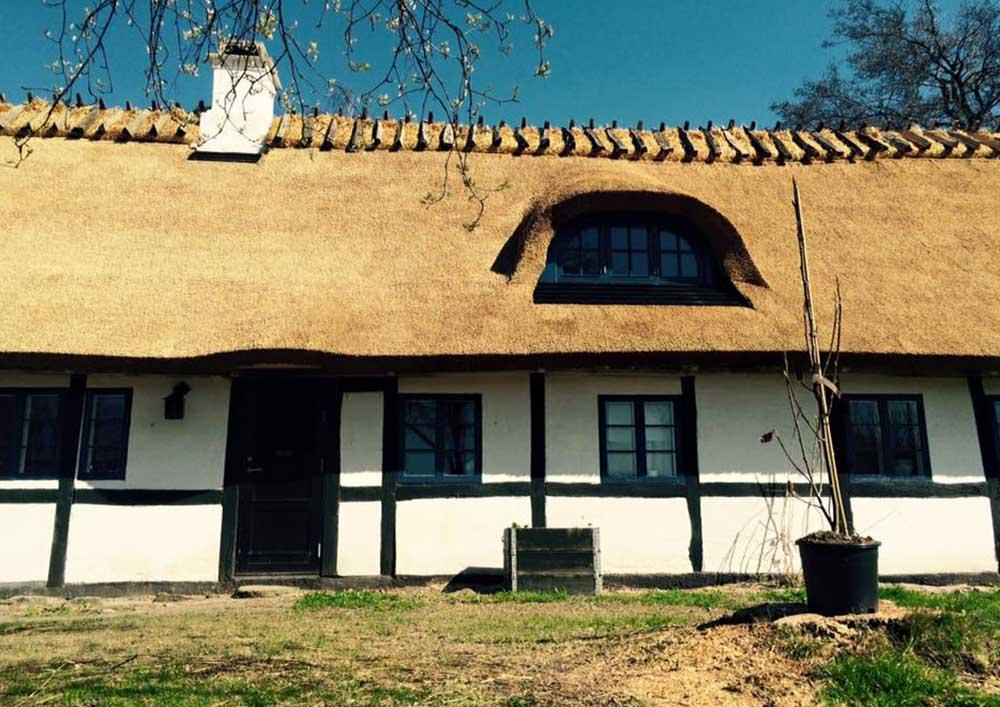 Langt hus med stråtag og kvist