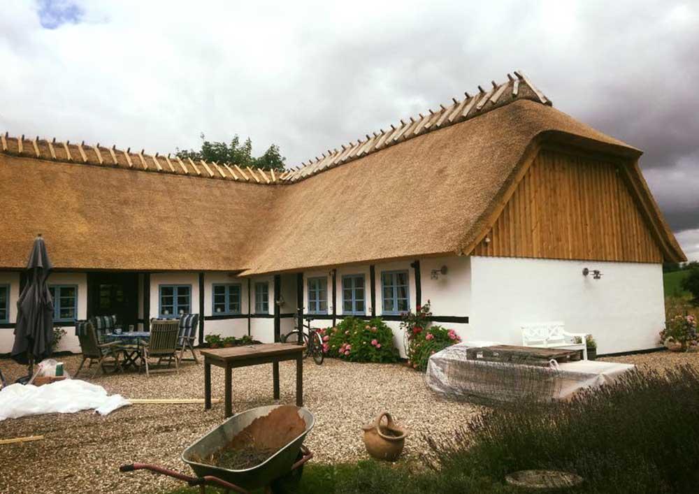 Stort hus med grusgård og stråtag